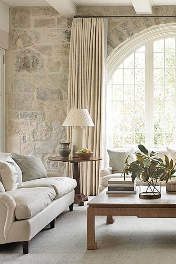 Interior design inspiration from a family room designed by Phoebe Howard with limestone wall, magnificent arched window, and white decor. - Interior design inspiration from a family room designed by Phoebe Howard with li.
