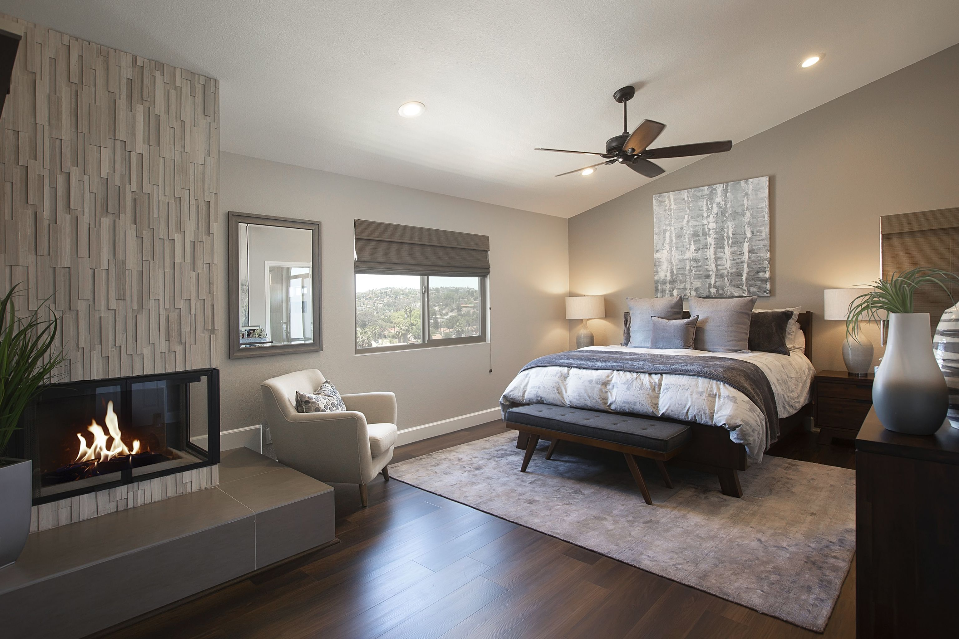 Master bedroom in warm greys with stacked stone fireplace san