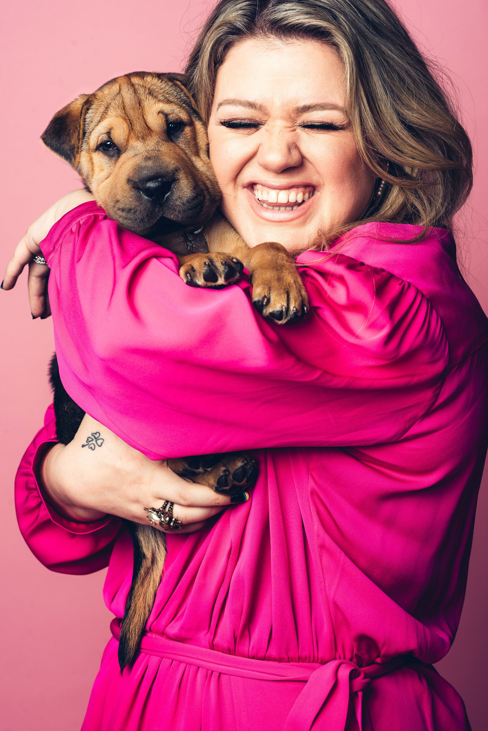 Kelly clarkson gets interviewed while playing with puppies