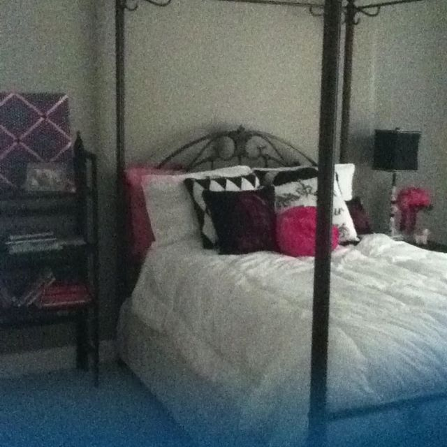 This is a Paris themed room! With a lot of pillows on the bed and black white and pink for the colors!