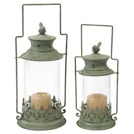 Set of two weathered metal lanterns with a copper verdigris finish and bird finials.   Product: Small and large lanternConstruction Material: Metal and glassColor: Copper verdigrisFeatures: Bird finialsAccommodates: (1) Candle each - not includedDimensions: 17 H x 7.25 Diameter (large)