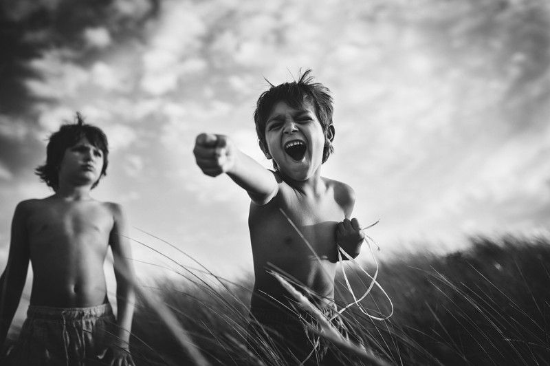boys playing in tall grass in France by Nadia Stone
