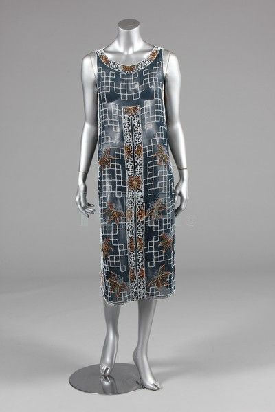 A beaded tunic-dress, late1920s, of midnight-blue muslin adorned with a lattice of white beads with oriental flowerheads in orange and silver beads, side slits, bust 92cm, 36in Provenance: Anne Dettmer collection
