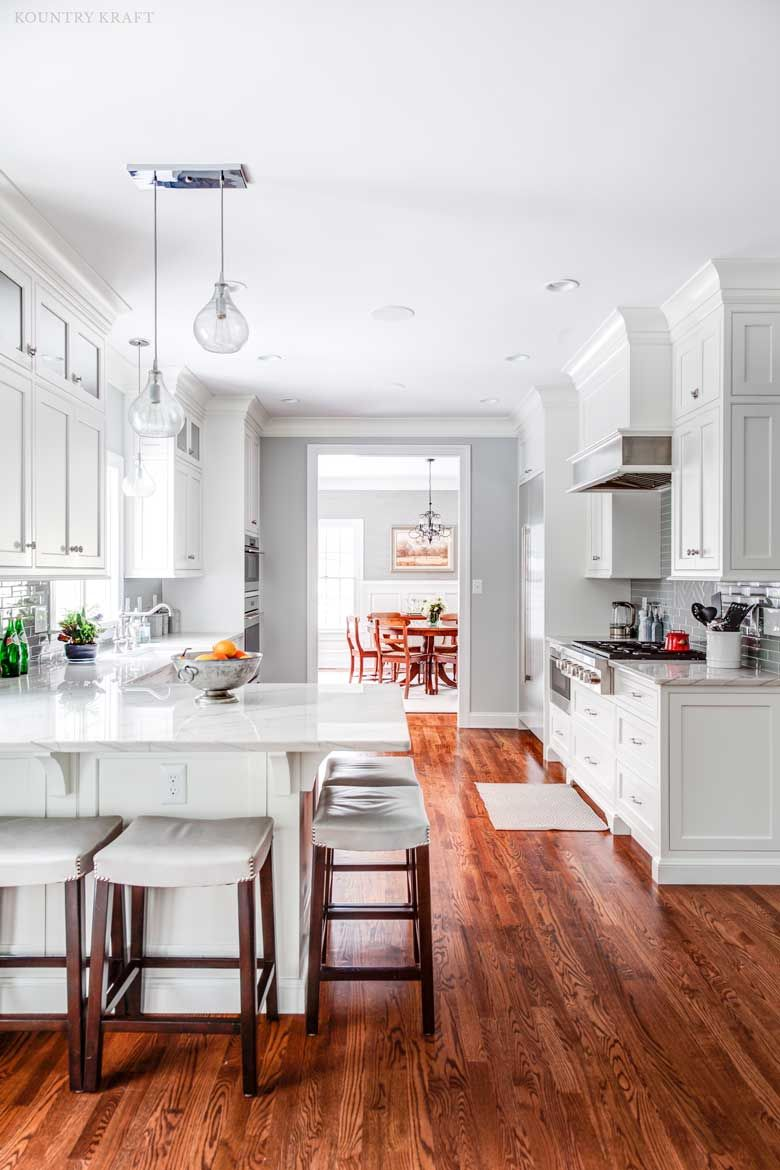 Five stools under an L-shaped counter and hard maple cabinets ...