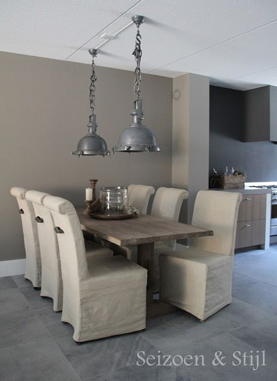 Wooden table  linen slip cover dining chairs industrial lighting  mushroom  colour wall. Wooden table  linen slip cover dining chairs industrial lighting