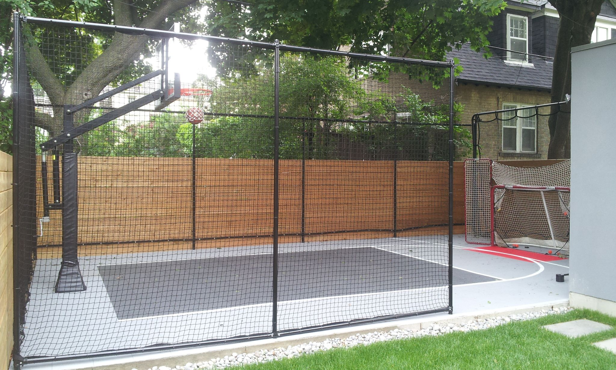 small side yard basketball court w boxwood and net barriers