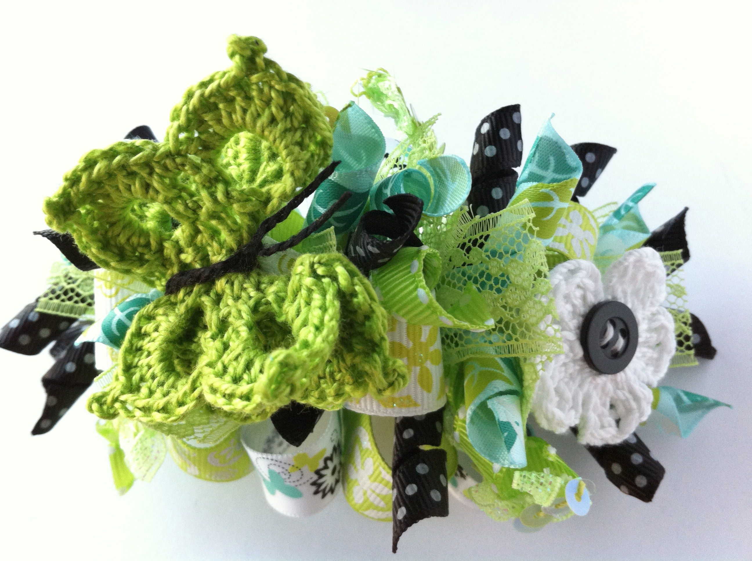 Loopy hair bow with crochet butterfly and flower.