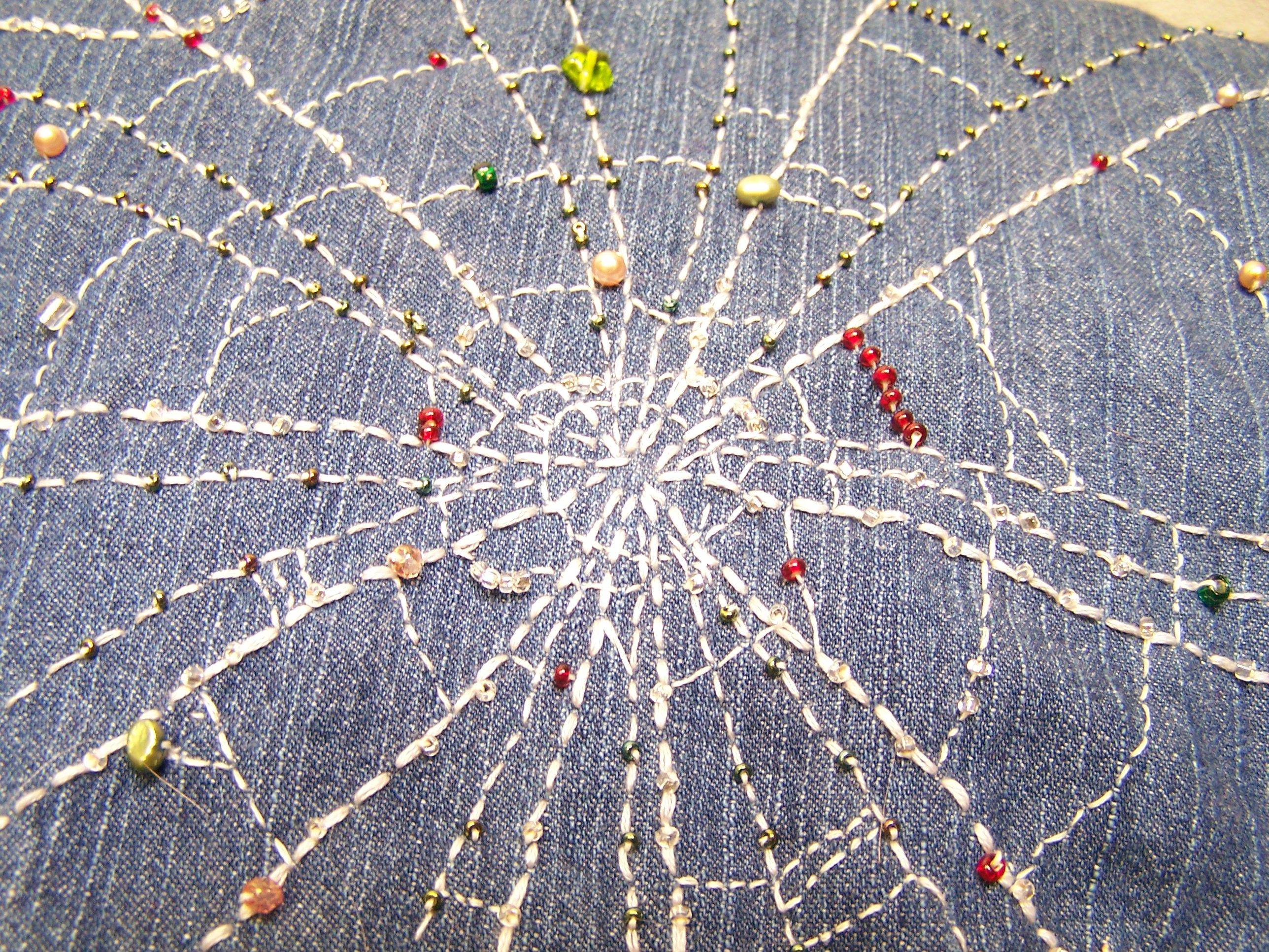 Ucycled denim jacket, sleeves and collar removed, with spiderweb embroidery and beading. Close up view. Work done by Sharon Robb-Chism
