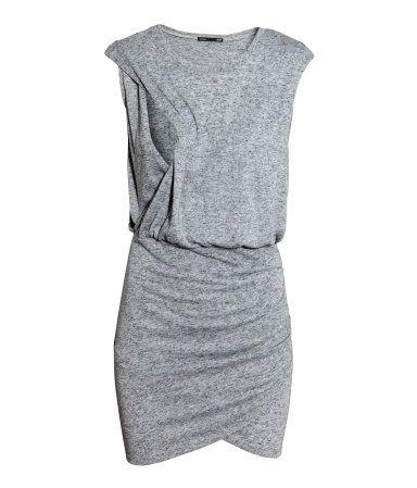 Ærmeløs kjole i meleret jersey med indvævet hør. Den har indertop i slå om-facon og overdel, der er åben i siderne, så amningen bliver nemmere. Kjolen er skåret med elastik i taljen og er i slå om-facon foran og med rynkeeffekt i den ene side.