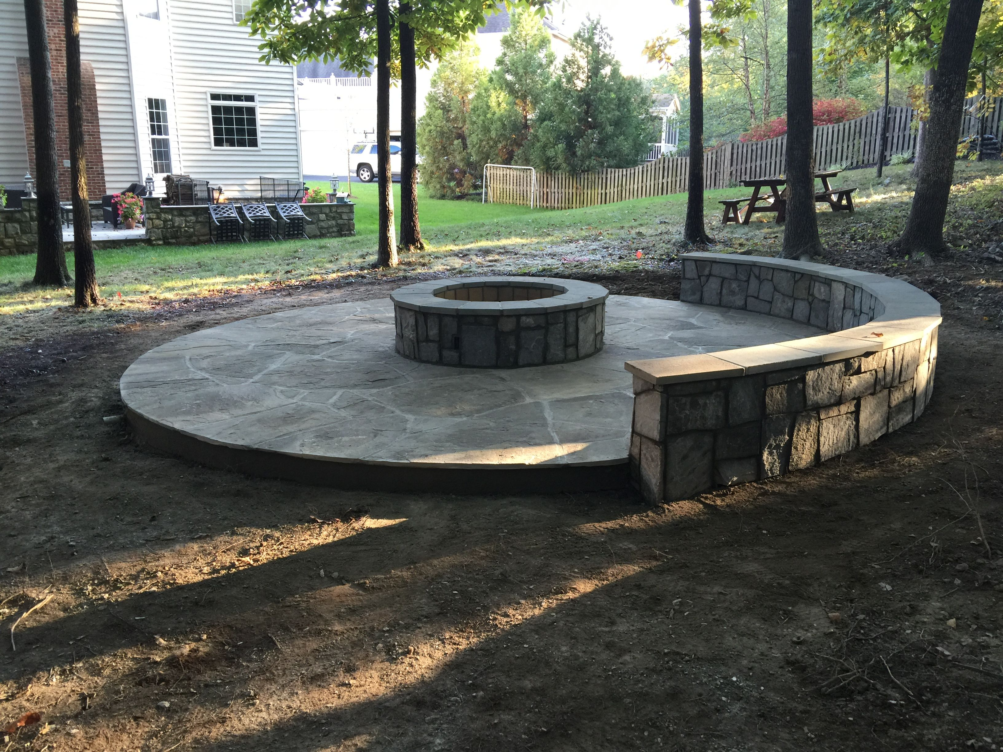 Circular Flagstone Patio With A Fire Pit And Stone Seating