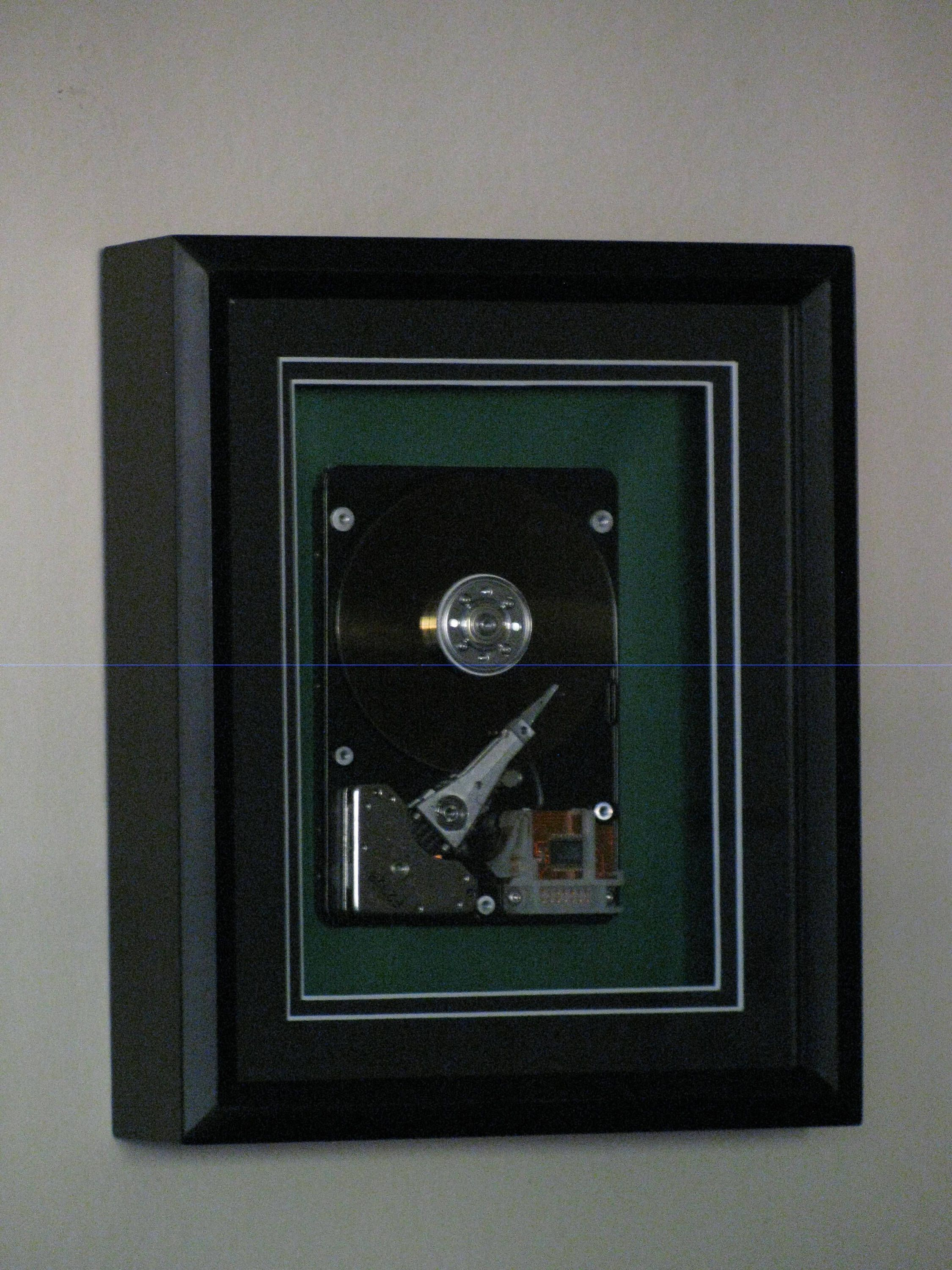 Computer hard drive enclosed in 8x10 black shadow box with a black ...