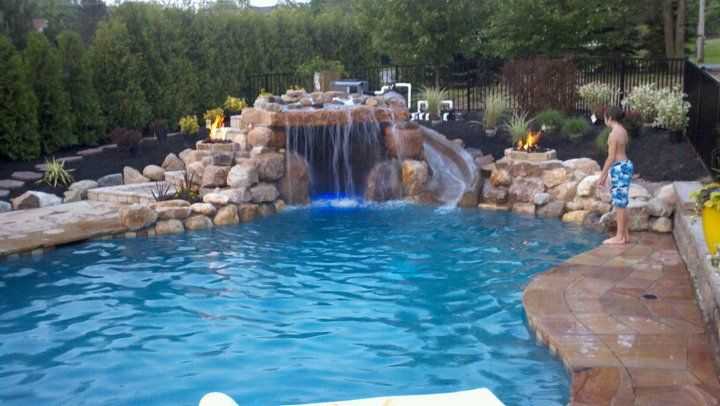 freeform gunite pool with beach entry grotto water fall fire bowls and shotcrete water