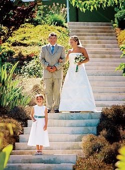 """Megan and Dave in Malibu, CA. The flower girl, Megan's sister, leads the bride and her father down a dramatic staircase at Rancho Chiquita, where the outdoor ceremony took place. """"My dad was going so fast, I was afraid that I was going to fall down the steps,"""" Megan says."""