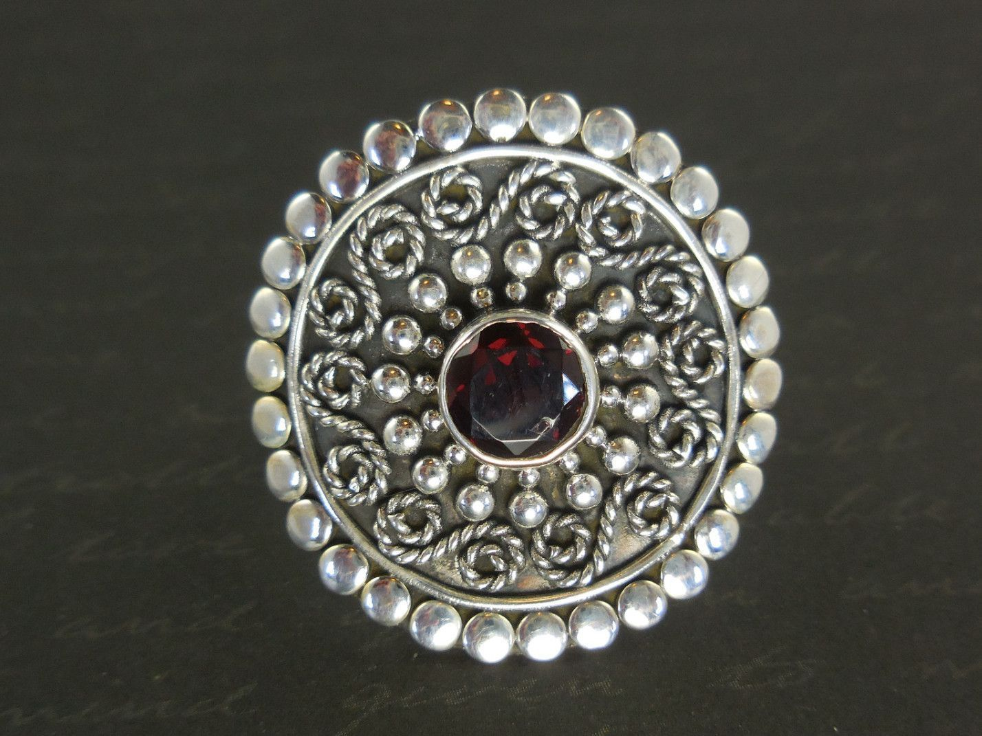 Made with 7mm round faceted garnet gemstone, sterling silver wire and metal. Size 7.0