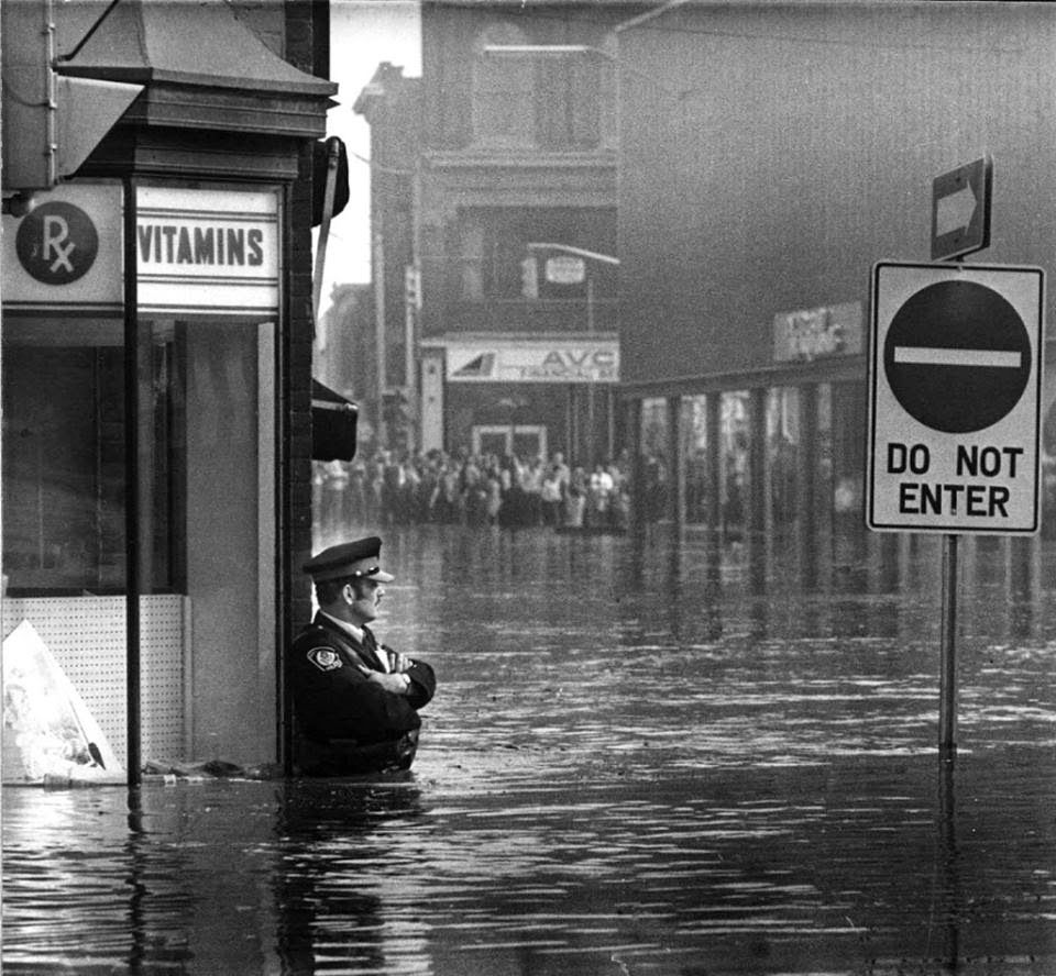 Canadian police officer guarding the pharmacy in waist-high flood waters in Galt, Ontario, 1974