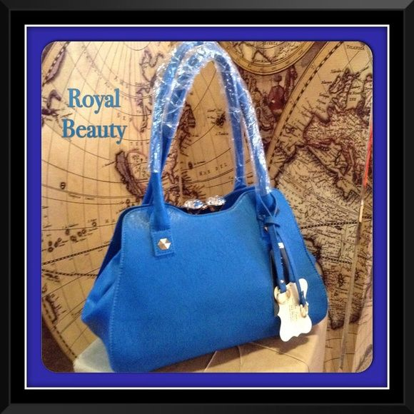 Royal Blue Handbag-(NO BUNDLE ITEM PLEASE) This beautiful bag features a kiss lock closure. Faux leather material. Fully lined with inside pockets and one exterior zipper pocket. Includes shoulder strap. Metal feet on the bottom for added protection.Measures 13W X 10H X 6D (This closet does not trade or use Paypal.) Bags