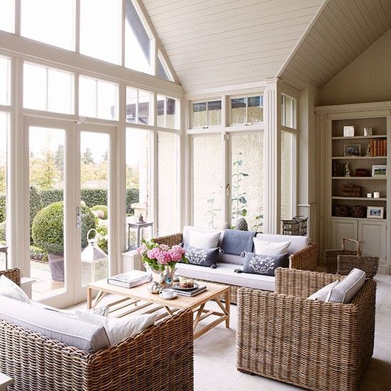 Smart wicker seating adds texture and a panelled ceiling complements the soaring windows in this country conservatory.
