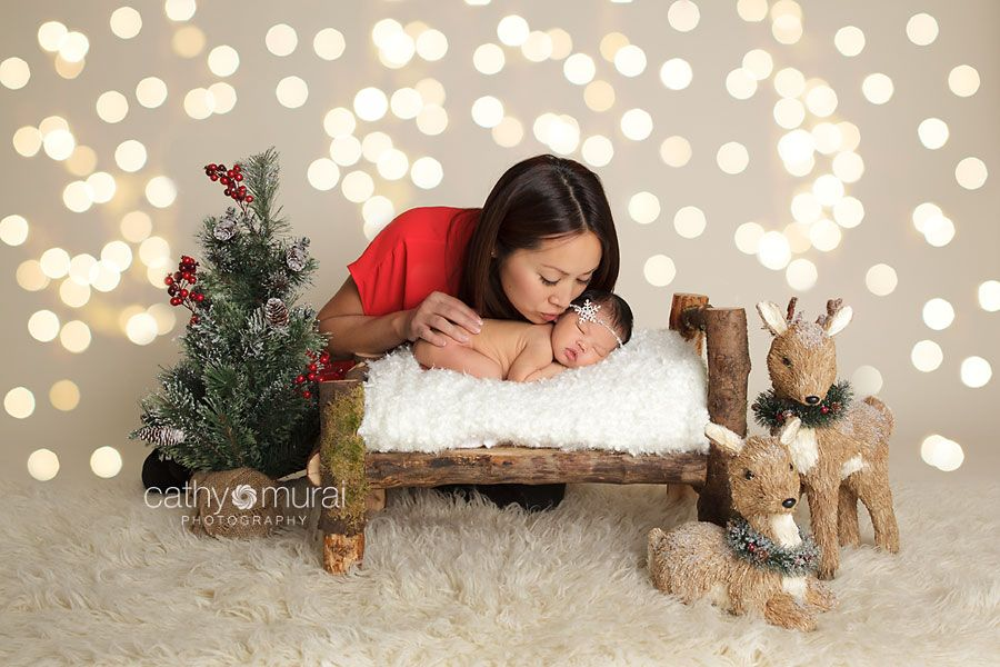 Beautiful mom kissing her newborn baby girl on the wooden bed during Christmas newborn portrait session. Edited with Christmas lights backdr...