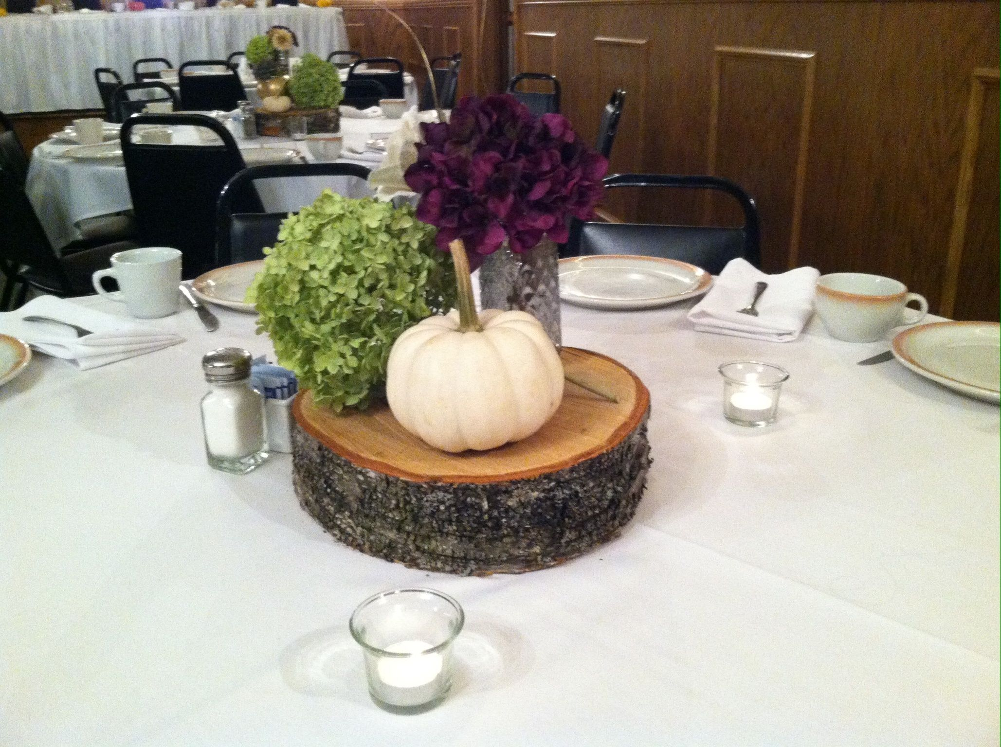 Log centerpiece with white pumpkin green and purple