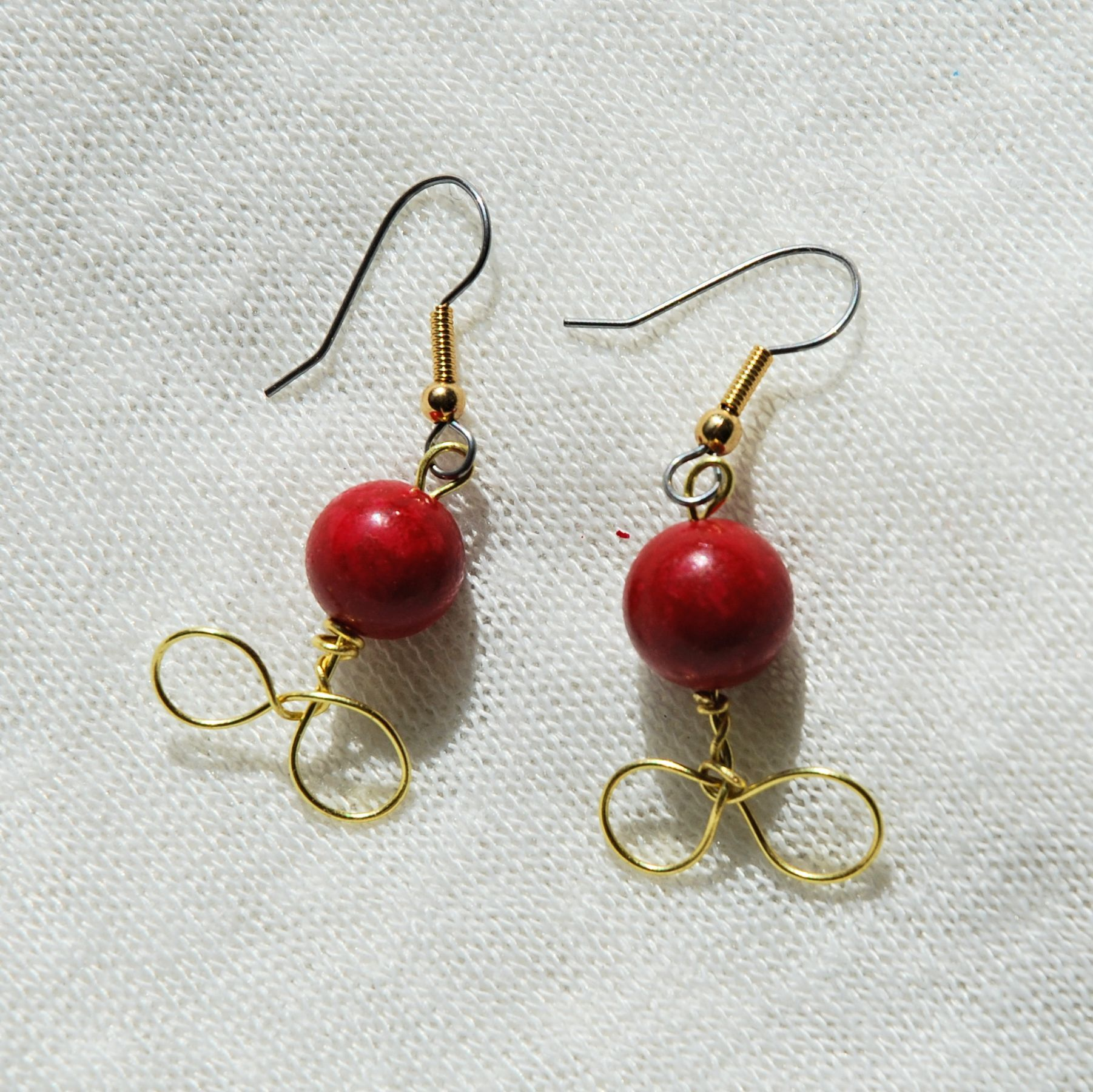 These earrings feature red sphere beads and have a brass wire-wrapped design!