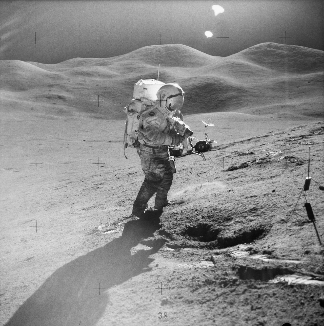 || Astronaut David R. Scott, commander, standing on the slope of Hadley Delta, uses a 70mm camera during Apollo 15 extravehicular activity (EVA) on the lunar surface. He is 10.5 miles (or 17.5 kilometers) from the base of the Apennine Mountains seen in the background.