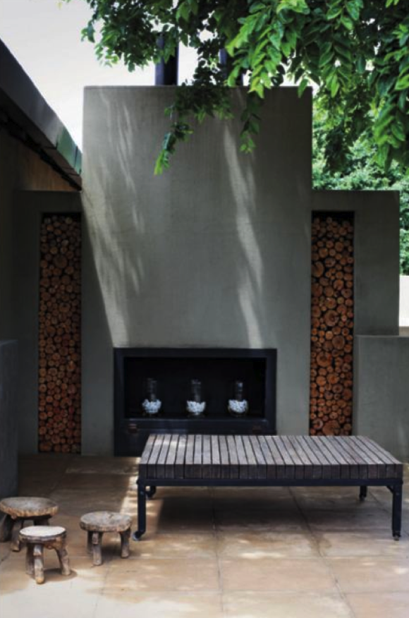 Contemporary stucco outdoor fireplace. Fire wood storage is used ...