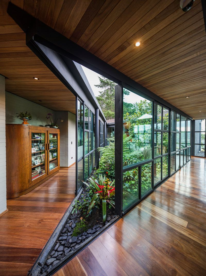 A central open-air garden filled with plants connects the wings of this modern house, with sliding glass walls opening the garden to the interior.