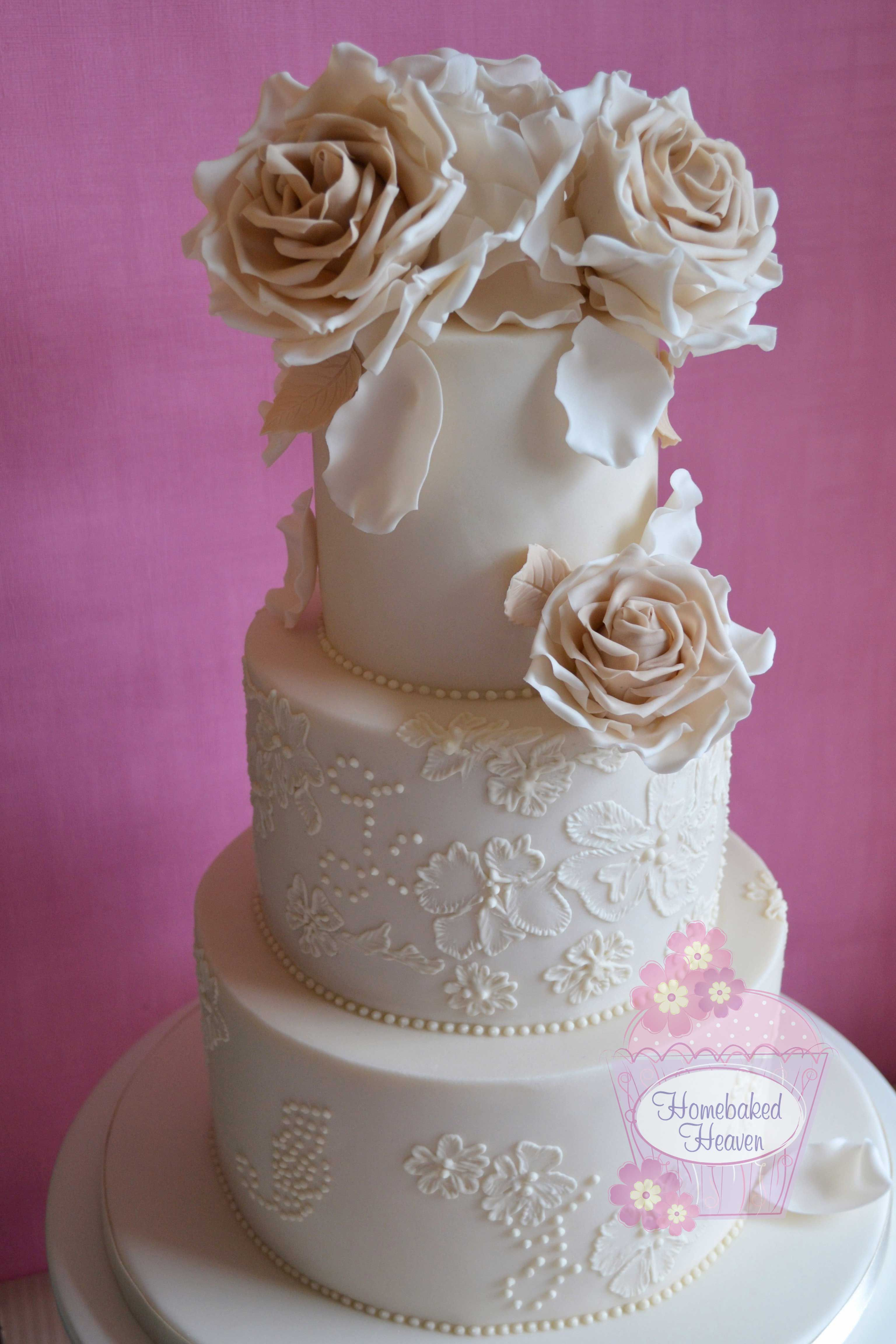 Ivory wedding cake with beige roses to match the bridesmaid