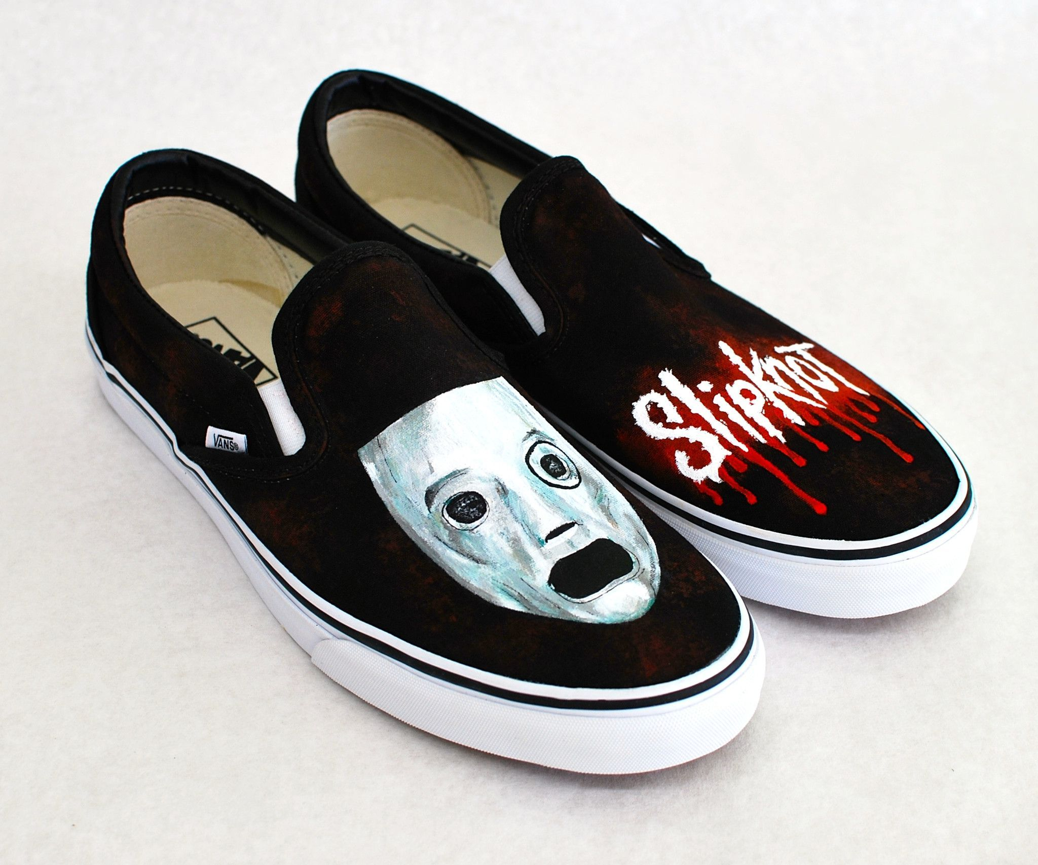 These black canvas Vans Slip ons are Slipknot theme. The shoes feature the Corey mask on one shoe and a Slipknot style logo on the other shoe. Both shoes are covered in a hand painted red blood patter