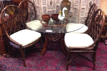 "Dark rattan dining set with four handsome arch-back chairs suitable for dining room or kitchen. 48"" diameter glass top. SOLD"