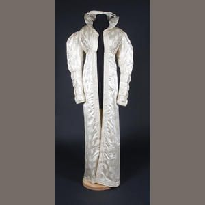Bonhams. An early 19th century redingote of figured cream silk.  The redingote coat is decorated down the centre front opening edges with lines of corded self-fabric bands, with the same style of bands circling the sleeves and hem, the high bust is covered in raised floral work, loop cord braiding and thread covered beads, with a large collar, and gathering to centre back, with bow decoration.