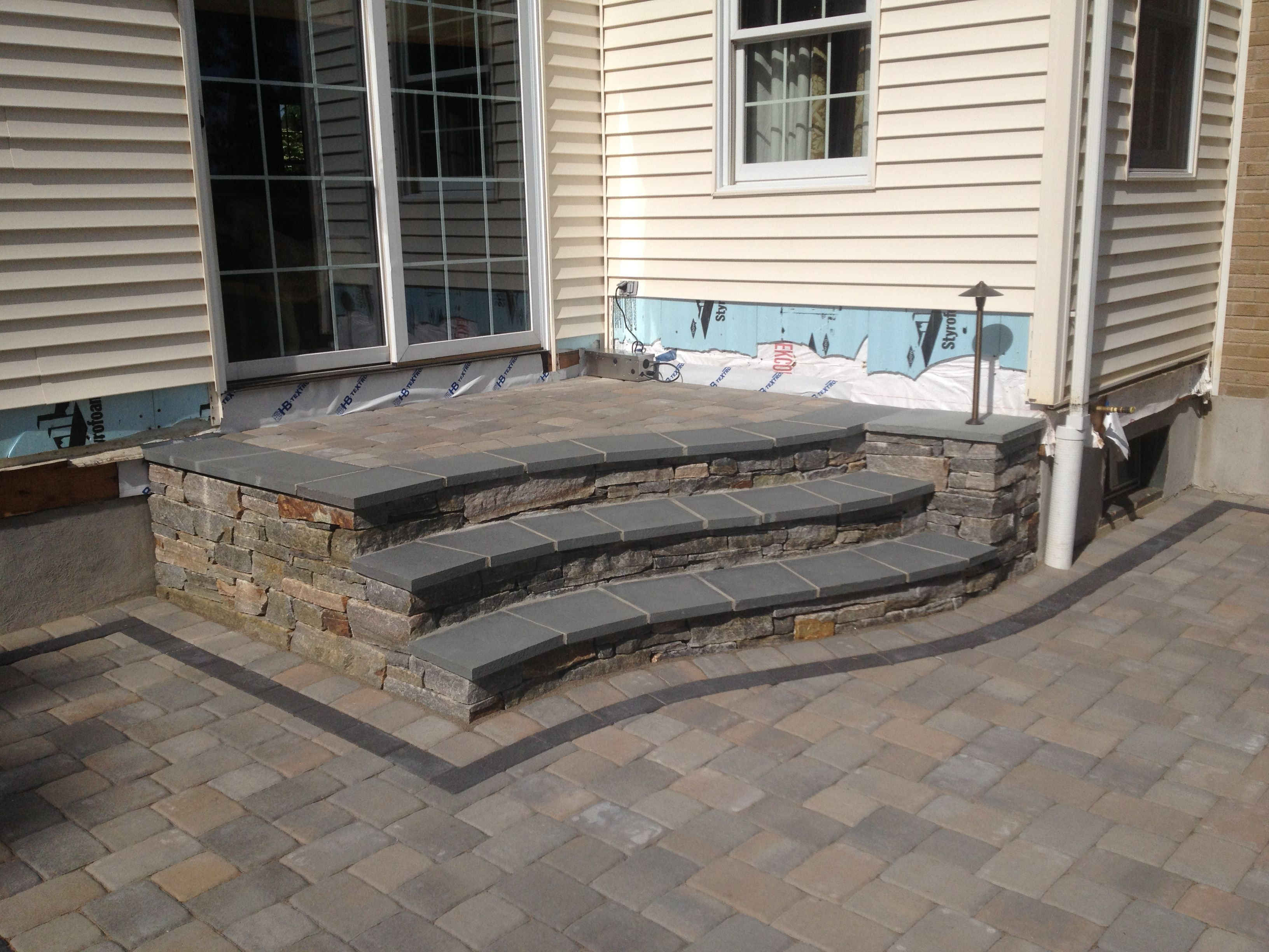 Natural stone steps with a blue stone cap leading to paver patio