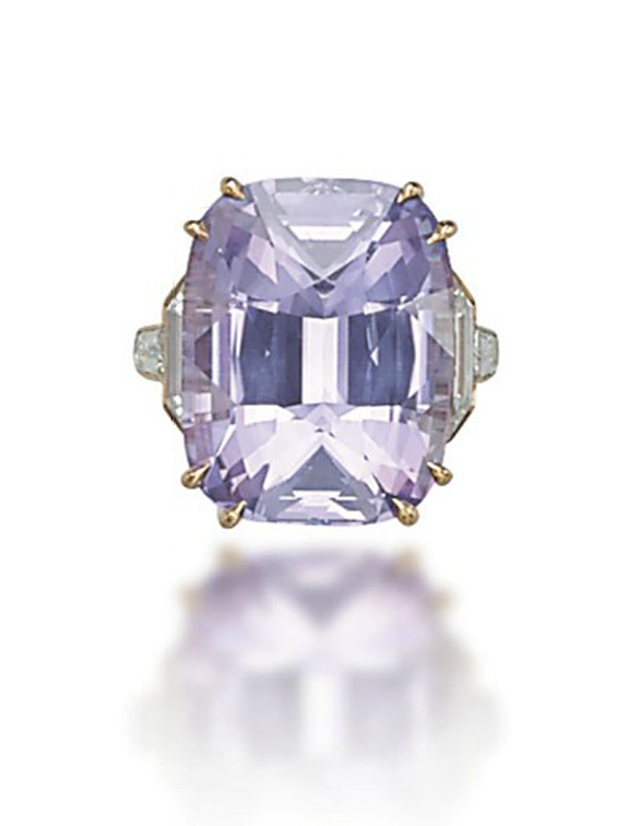 A COLOURED SAPPHIRE AND DIAMOND RING. Set with a cushion-shaped pink-purple sapphire, weighing approximately 27.22 carats, to the fancy-cut diamond shoulders, mounted in gold.