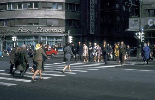 """Bucuresti, intr-o dimineata de octombrie, 1970. Intersectia CA Rosetti – Bd. Magheru. In coltul din dreapta, o bucata din blocul Scala, ce se va prabusi sapte ani mai tarziu, in 4 martie, in timpul cutremurului. In coltul de vis-a-vis, Lacto-Bar Dorna. Se putea manca dimineata cu 1 leu un iaurt+o painisoara. De remarcat """"traficul"""", doar un singur fericit posesor al unui Ford Capri, cea mai de fitze masina in epoca. In spate, parcat, un VW broscuta, la mana a doua, din ce"""
