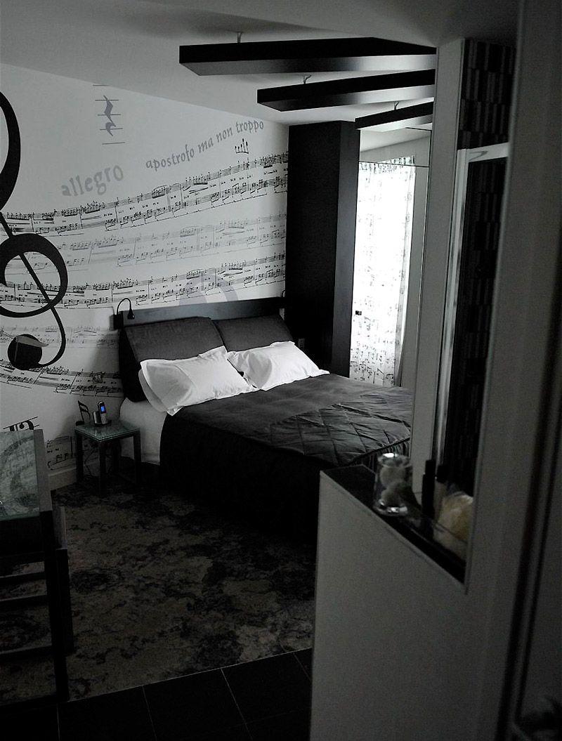 Amenajare dormitor in negru si alb: perete desenat cu portativ si note muzicale