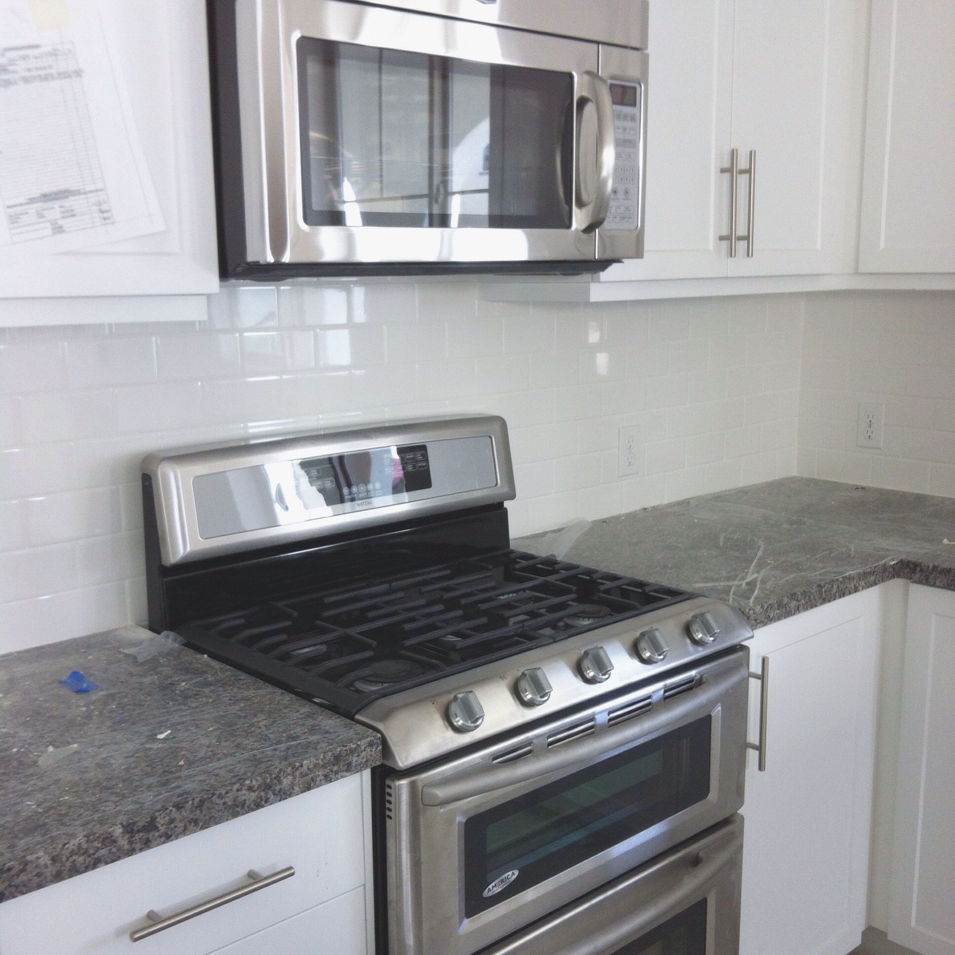 - White Subway Tile Backsplash And New Caledonia Granite Counter In