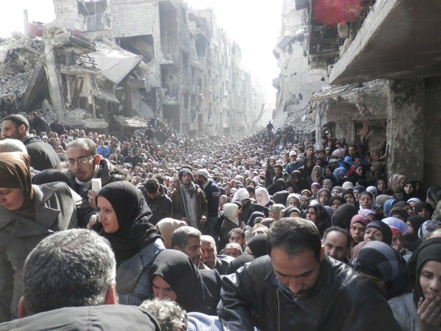Nel campo profughi palestinese di Yarmouk, a sud di Damasco, la popolazione non ha cibo. Nell'immagine Reuters, un impressionante fiume di persone     residenti  mentre  aspettano di   ricevere aiuti   alimentari distribuiti   dalle Nazioni Unite . Le  potenze mondiali   hanno   approvato una