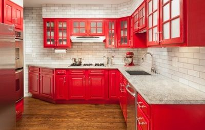 The bold red cabinets make a statement complimented perfectly with the sustainably crafted Fireclay Tile.   #sustainable #ecofriendly #bold #kitchen #backsplash #white #subway #modern #tile #red   NATURAL BUILDING DESIGNS