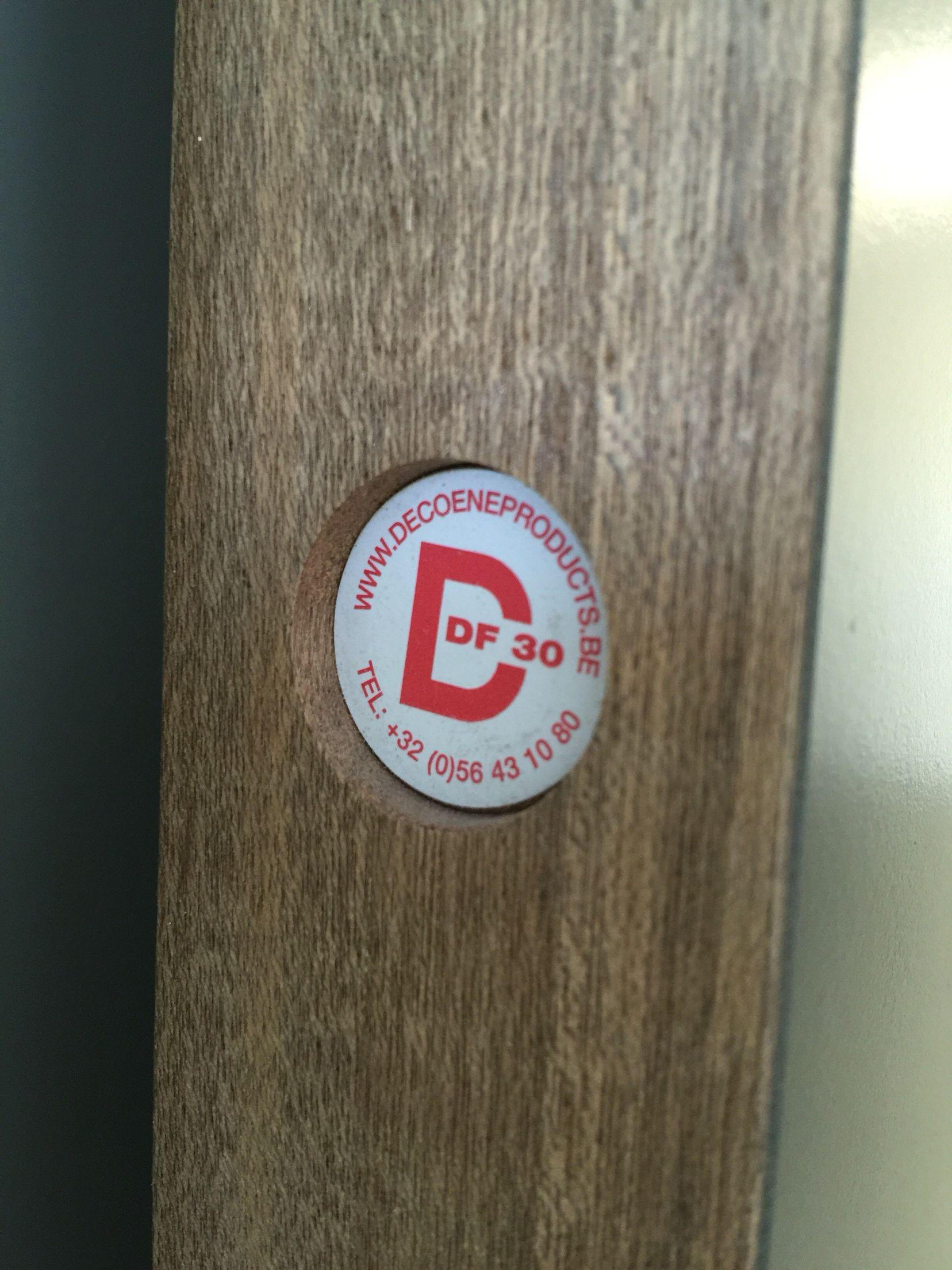Dit is een logo sticker aan de achterrand van een deur dat een punt vormt.