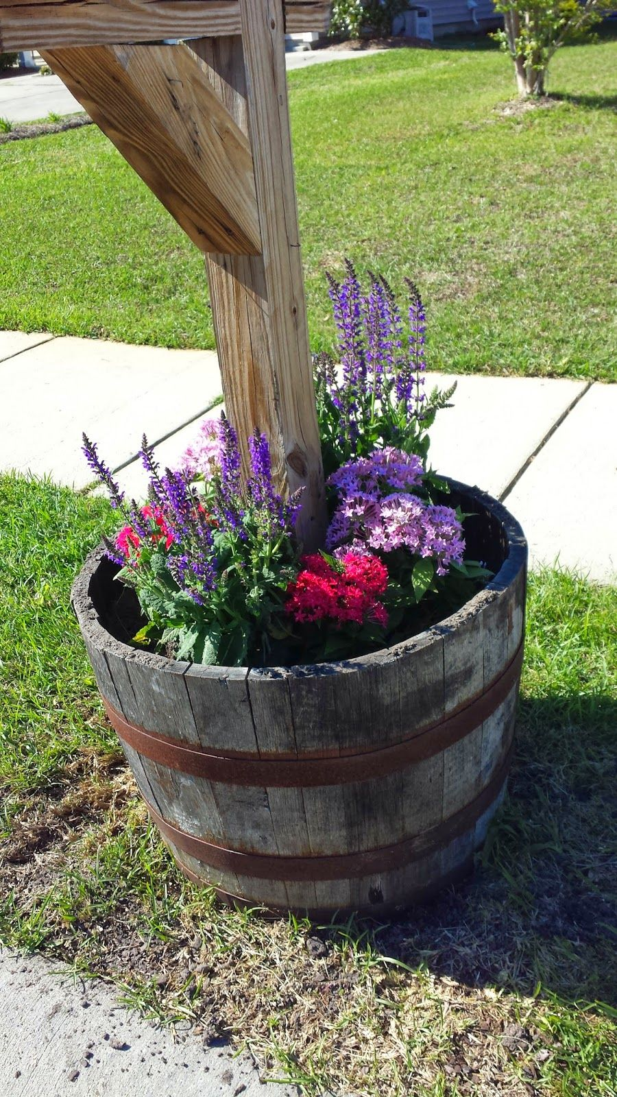 Mailbox whiskey barrel filled with spring flowers home for Wooden barrel planter ideas
