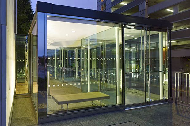 A frameless glass entrance portal separates the new