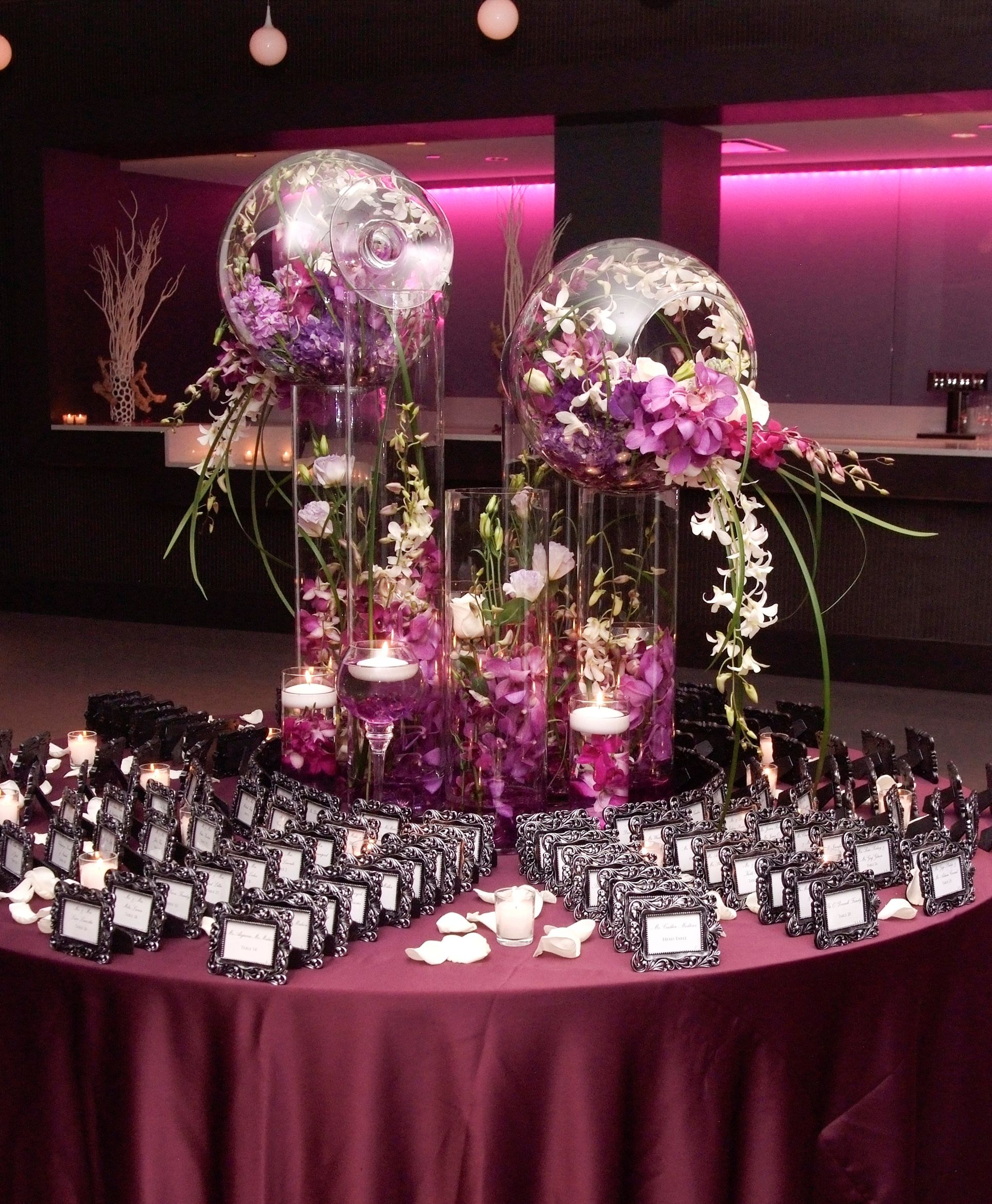 glass cylinder decorations overflowing with exotic flowers the perfect wedding place card table