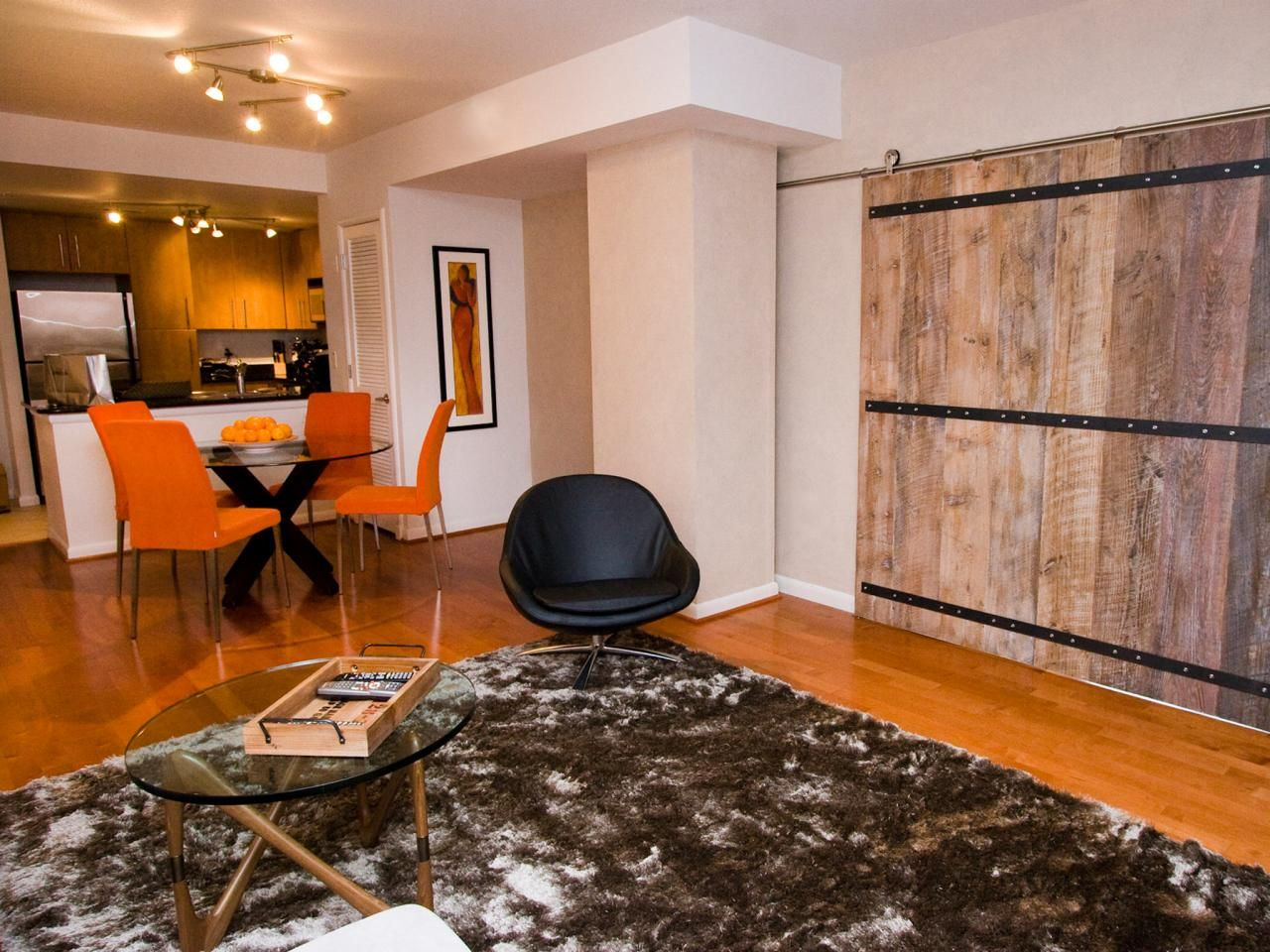 A sliding barn door leads into this shared transitional living room and dining room space. A shaggy area rug defines the living room area with a nearby dining table and bright orange chairs that provide a colorful spot to enjoy a meal.
