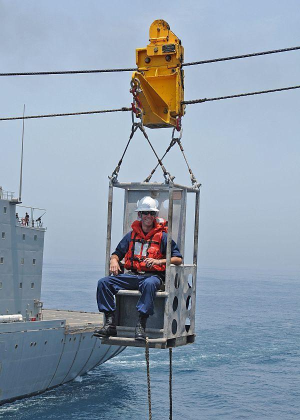 Boatswain's Mate 1st Class Ryan Abbott rides a boatswain's ...
