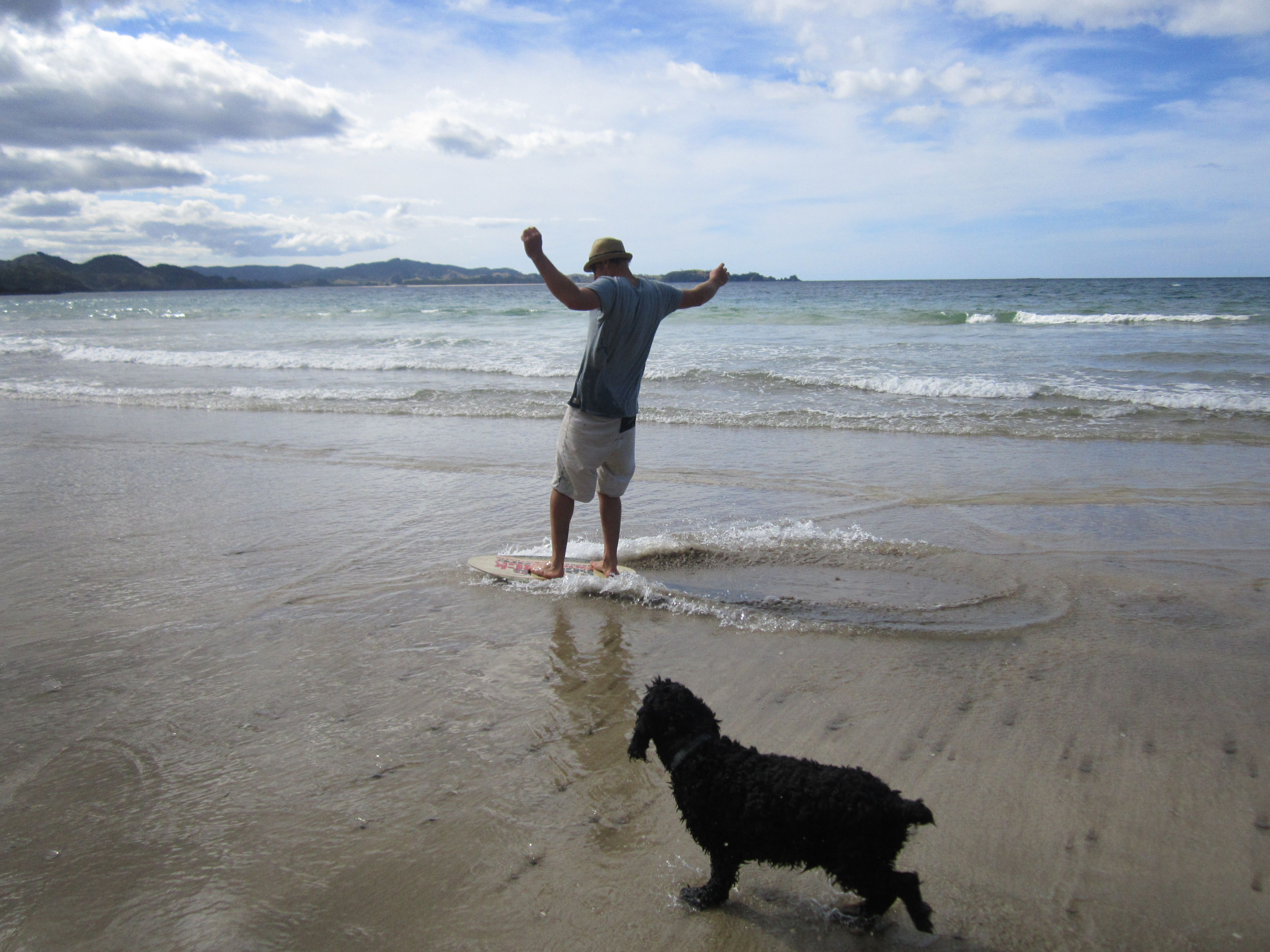 Todd skim boarding at Matapouri with Snuffles