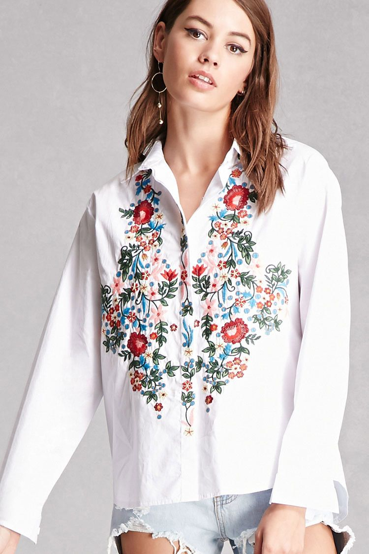 A crisp woven shirt featuring front floral embroidery, a basic collar, long sleeves with button cuffs, a hidden button front, and a curved high-low hem.