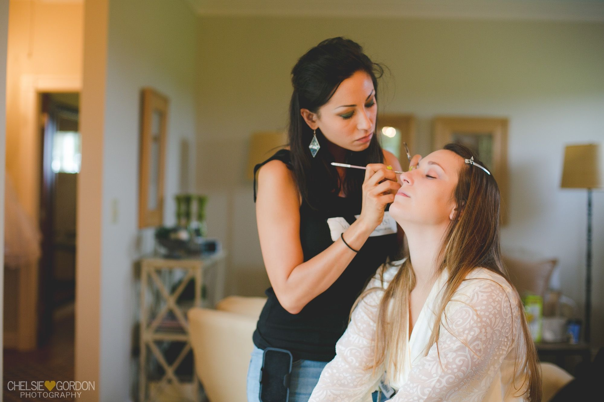 bride having her hair and makeup done on her wedding day
