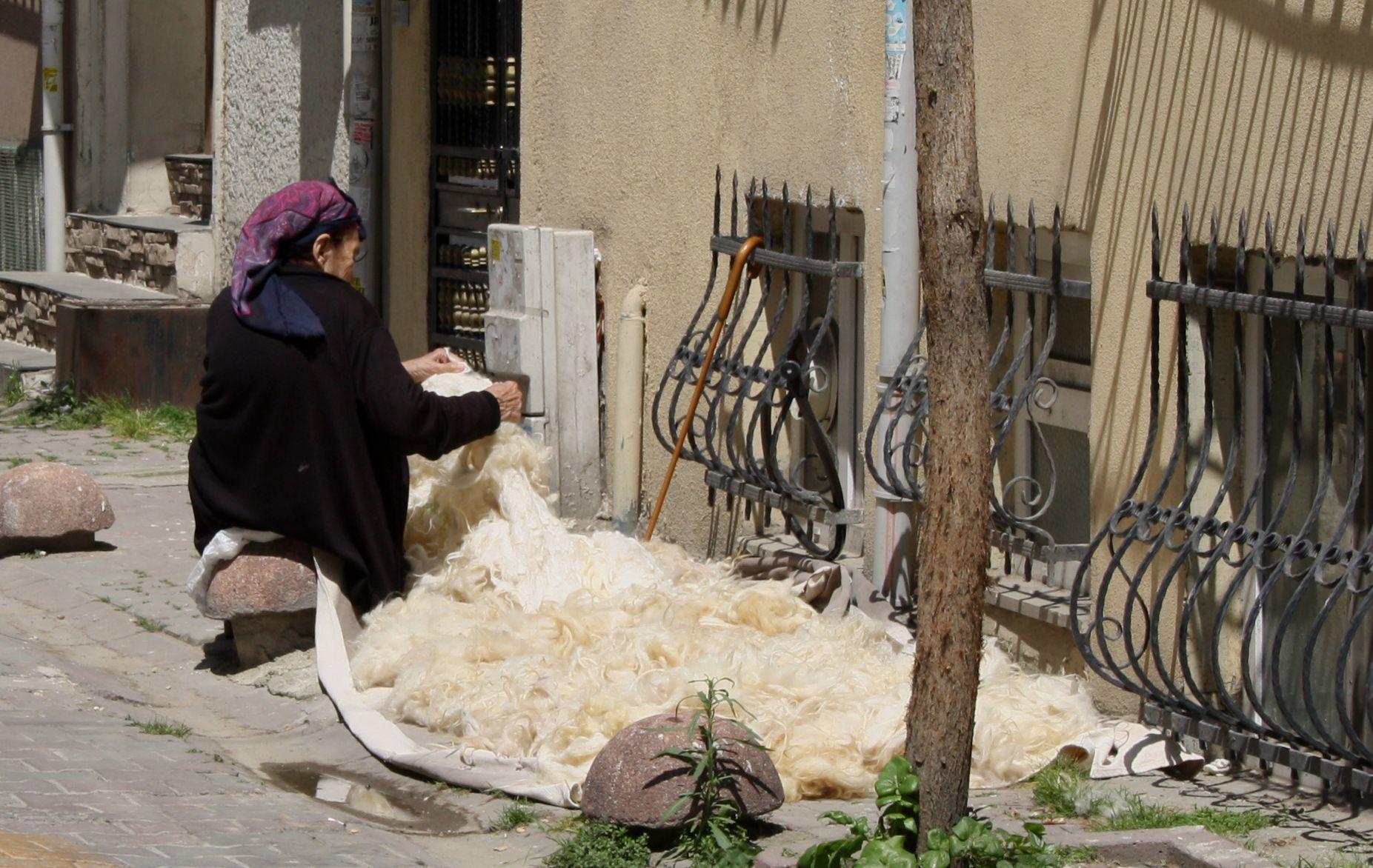 Woman preparing freshly shaven sheeps wool in downtown Istanbul