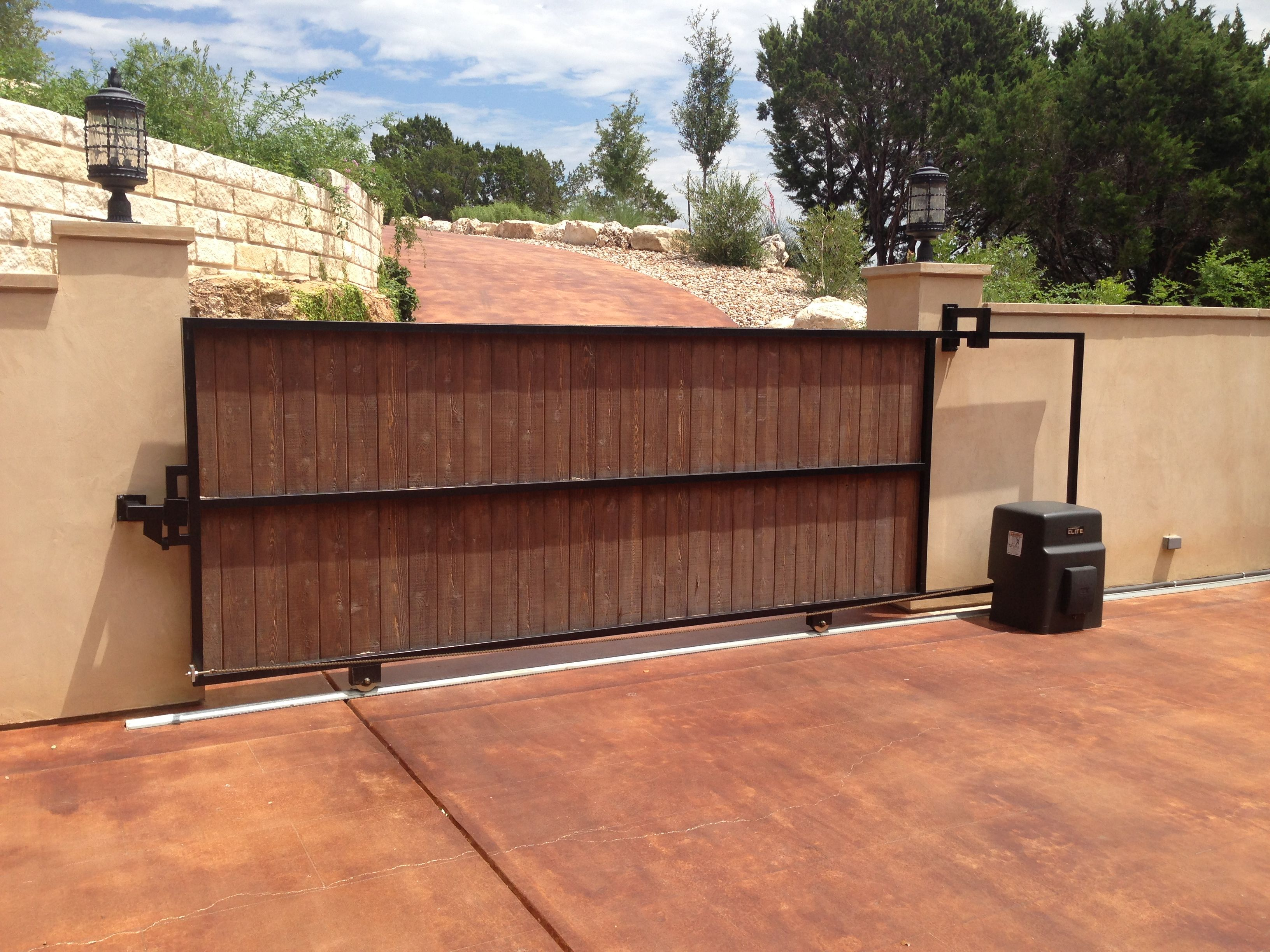 Sliding driveway wood covered gate with metal frame with for Wooden sliding driveway gates