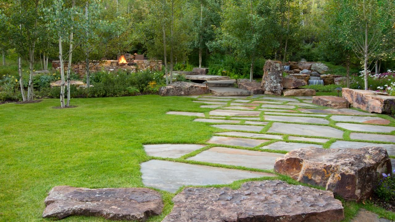 Rugged Rocks And Smooth Stone Pavers Are Scattered Along The Edge Of The  Lush Lawn Leading To The Fire Pit Patio.